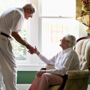Senior couple holding hands and smiling at each other.
